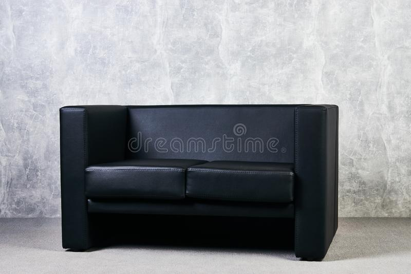 Black leather sofa against gray textured wall background. stock image