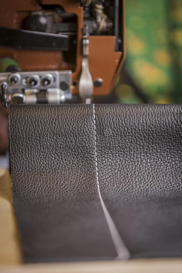Black Leather Stitching in Front of a Commercial Sewing Machine royalty free stock photos