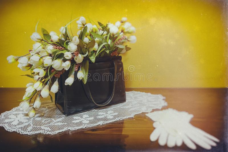 Black leather vintage purse filled with flowers standing on glass surface with white lace gloves like decoration stock photo