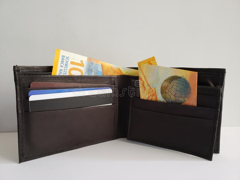 black leather wallet with  swiss banknotes and white background royalty free stock photography