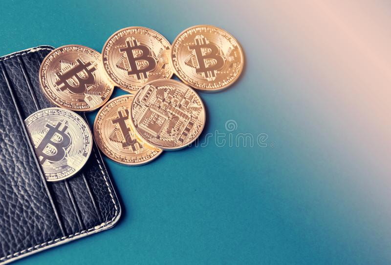 Black leather wallet on a blue background with several gold and silver coins of bitcoins falling out of their pockets. stock photos