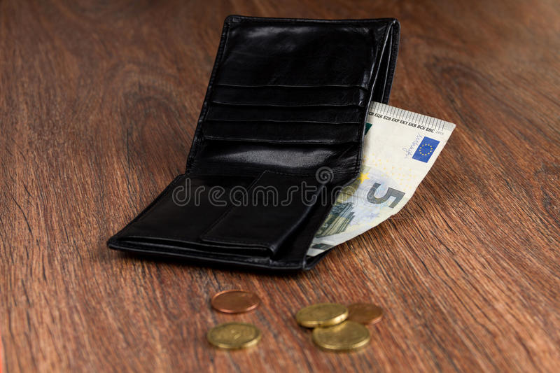 Black leather wallet with five euro and euro cents. Concept: poverty. Wallet of poor men / women with five euro and euro cents royalty free stock images