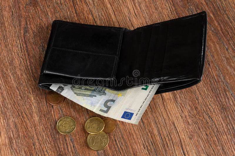 Black leather wallet with five euro and euro cents. Concept: poverty. Wallet of poor men / women with five euro and euro cents stock photography