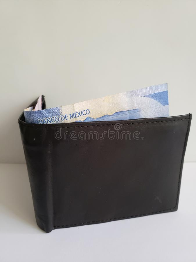 Black leather wallet with mexican banknotes and white background. Backdrop for announcements of trading and exchange, bank and commerce, price of buy and sell royalty free stock photography