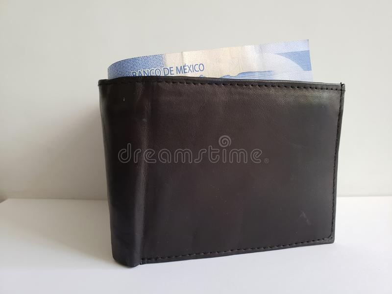Black leather wallet with mexican banknotes and white background. Backdrop for announcements of trading and exchange, bank and commerce, price of buy and sell royalty free stock images