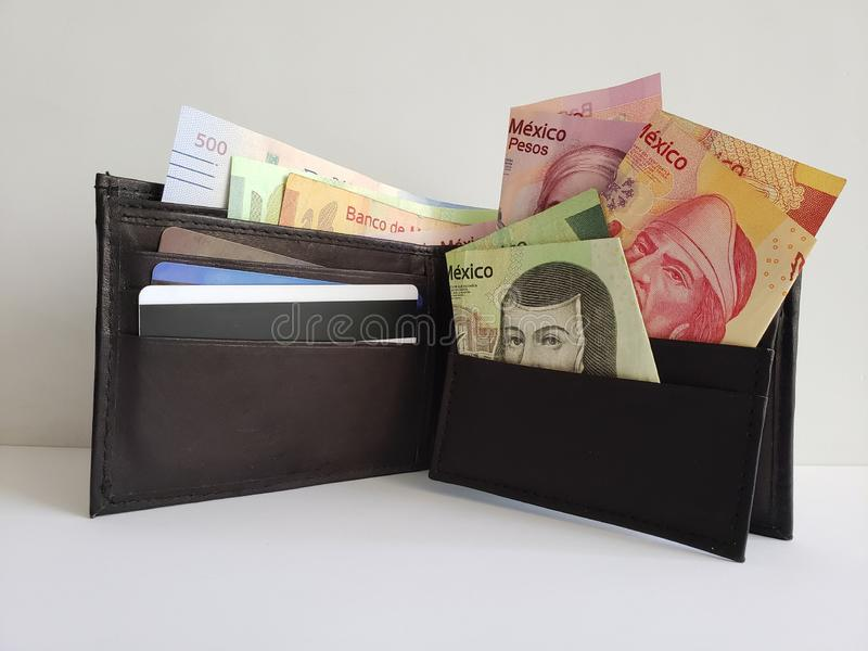 Black leather wallet with mexican banknotes and white background. Backdrop for announcements of trading and exchange, bank and commerce, price of buy and sell stock photo