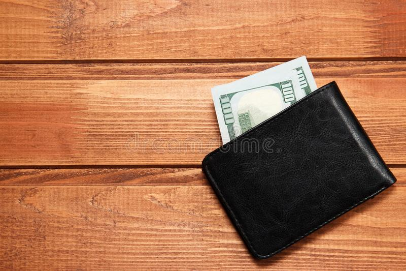 Black leather wallet with money on wooden background. Top view.  stock photos