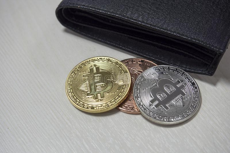 Black leather wallet on table with coins of bitcoins falling out of their pockets. The concept of crypto currencies royalty free stock photo