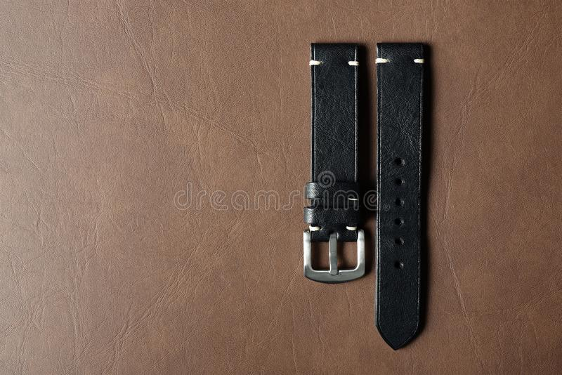 Black leather watch strap with stainless buckle on leather background, Craft and handmade watch bracelet. Black leather watch strap with stainless buckle on royalty free stock photo