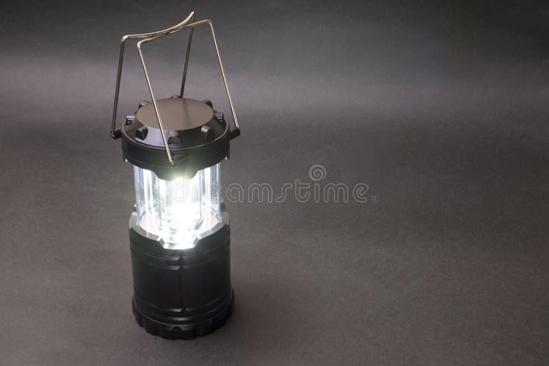 Black LED lantern. Lighting black LED lantern in front of dark background royalty free stock image