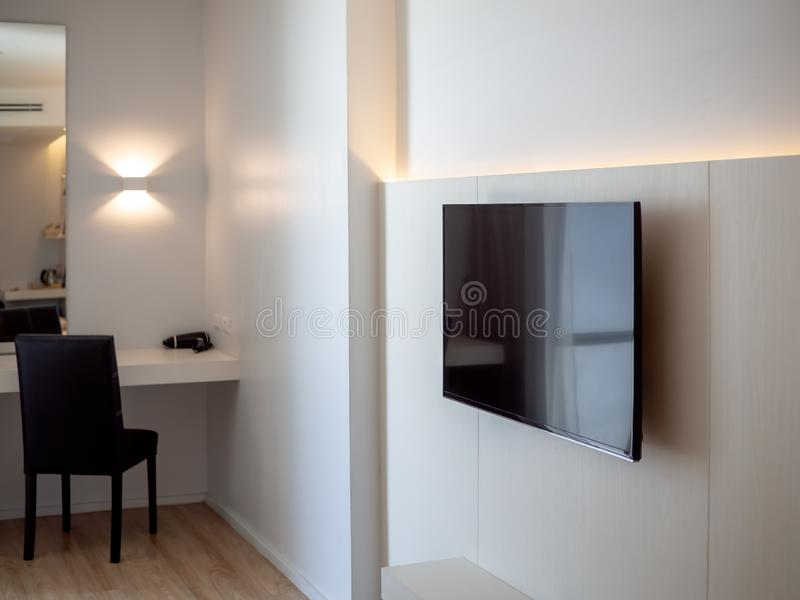 Black LED television on white wall near makeup corner with black chair in hotel room royalty free stock images