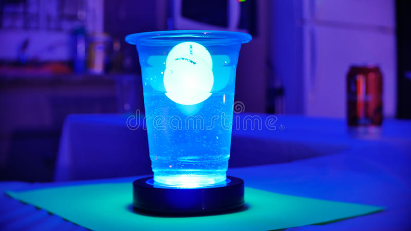 Black light beer pong party. Black light beer pong at a party stock photos