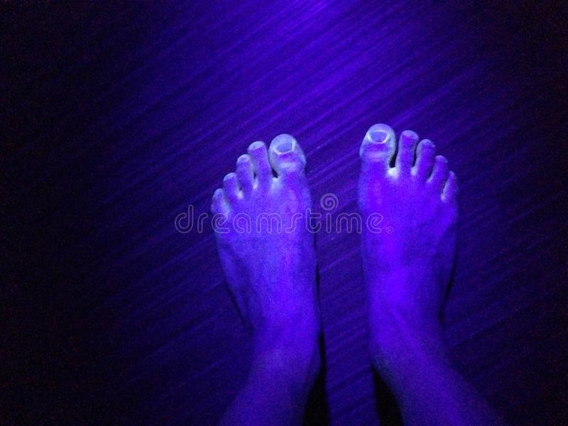 Black light on colorful feet royalty free stock photo