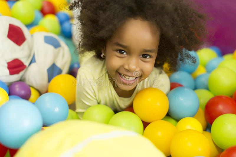 Black little girls in the playroom. Black little girl among the balloons in the playroom royalty free stock image