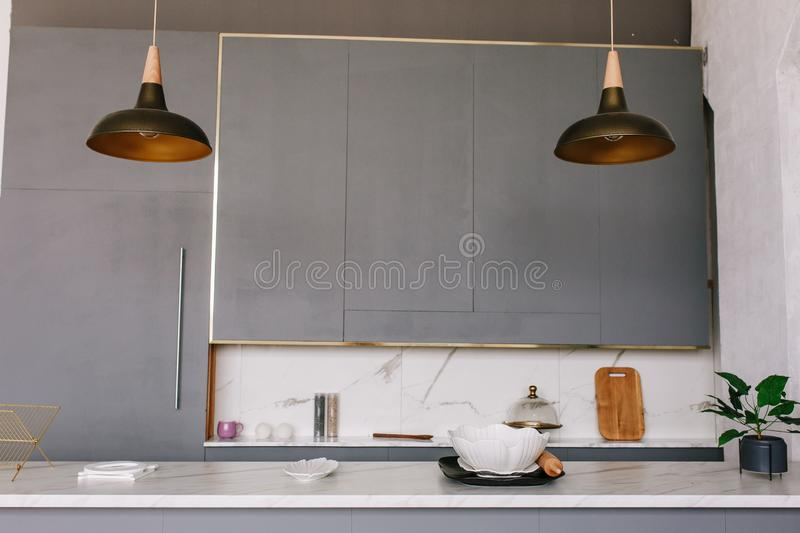 Black loft kitchen lamps in a modern style with gray cabinets, white lockers and shelves with accessories. There is a stock photo