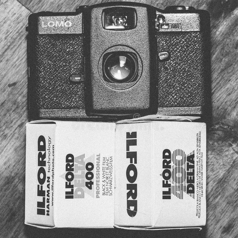 Black Lomo Compact Camera Beside Ilford Delta 400 Black & White Film Box royalty free stock photography