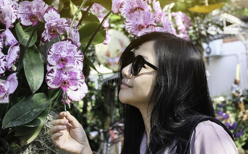 Black long hair Asian women wearing sunglasses looking violet orchid flower in garden in summer day light royalty free stock photo