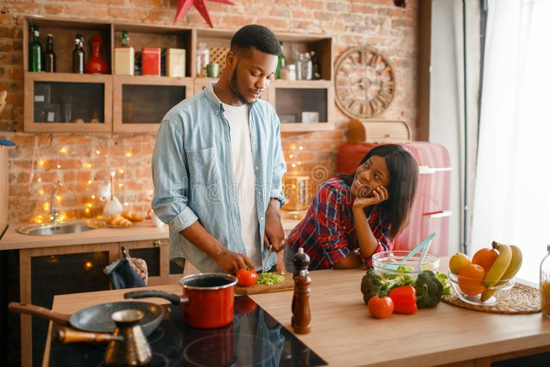 Black love couple cooking romantic dinner. On the kitchen. African family preparing vegetable salad at home. Healthy vegetarian lifestyle stock photos