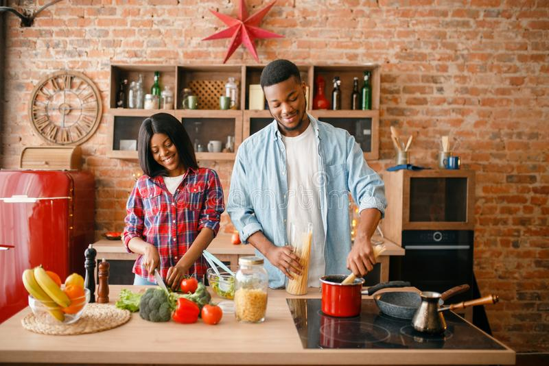 Black love couple cooking romantic dinner. On the kitchen. African family preparing vegetable salad at home. Healthy vegetarian lifestyle stock images