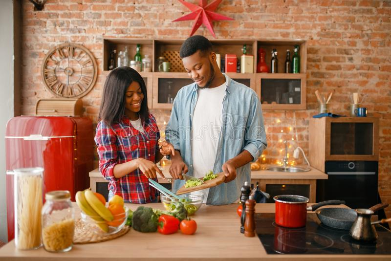 Black love couple cooking romantic dinner. On the kitchen. African family preparing vegetable salad at home. Healthy vegetarian lifestyle stock photography