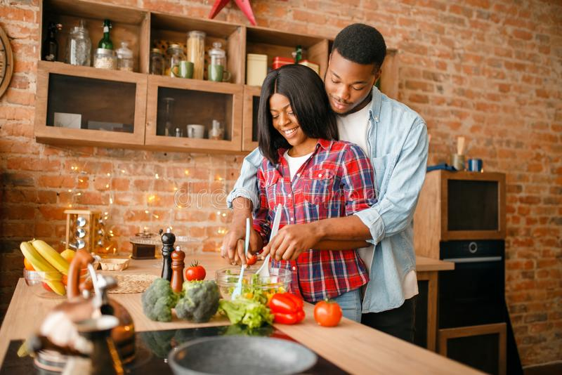 Black love couple cooking together on the kitchen. African family preparing vegetable salad at home. Healthy vegetarian lifestyle stock image