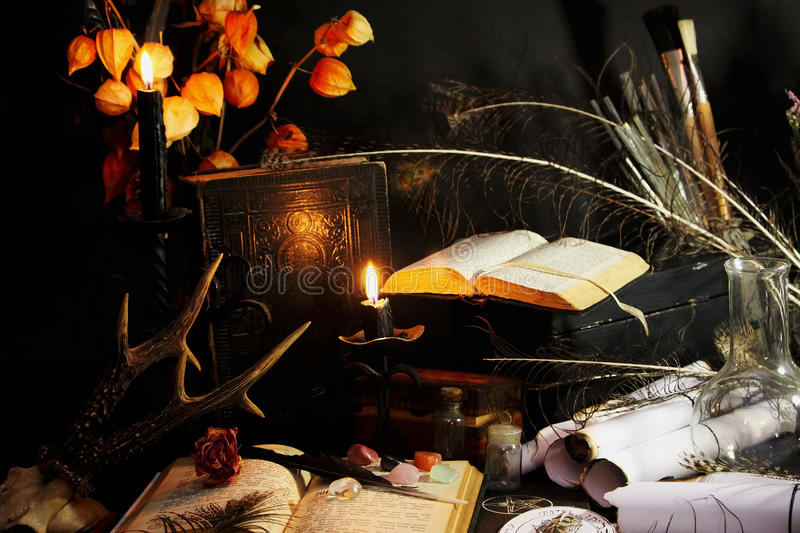 Black Magic. Antique Magic Book. Witchcraft background. Candle and alchemy ingredients around royalty free stock photography