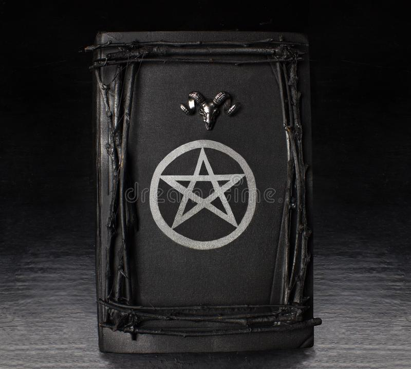 Black magic book with pentagram symbol. And ram`s head on. Halloween and occult concept stock photography