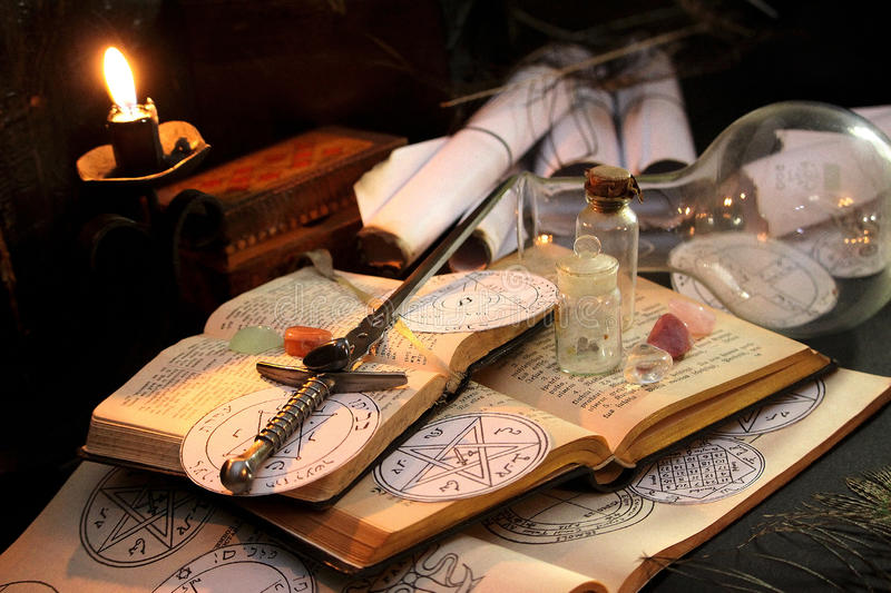 Black Magic Ritual. Antique Magic Book. Witchcraft background. Candle and alchemy ingredients around royalty free stock image
