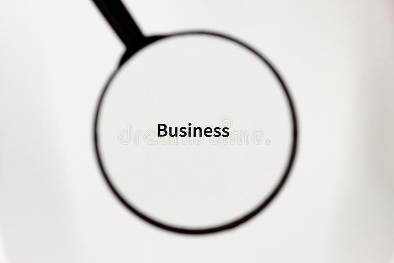 Black magnifier magnifies the inscription on a white sheet of paper. Black magnifier increases the inscription on a white sheet, mock up stock photo