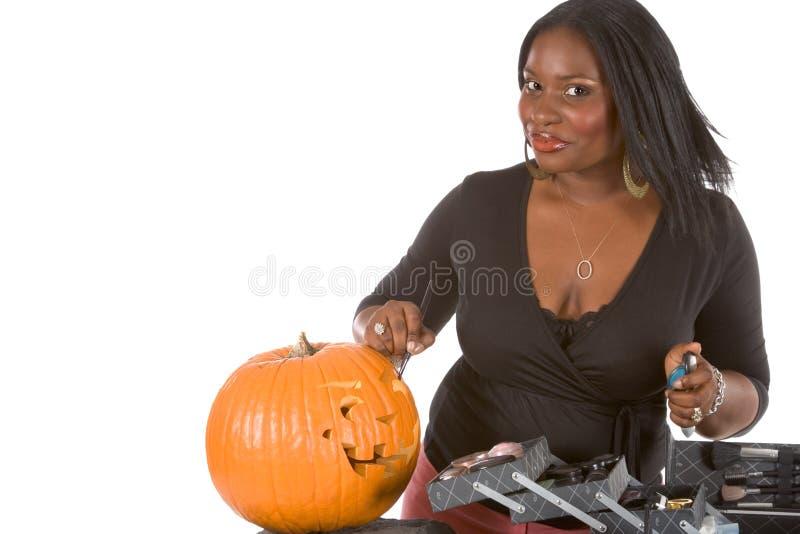 Black make-up artist decorating Halloween pumpkin stock photography