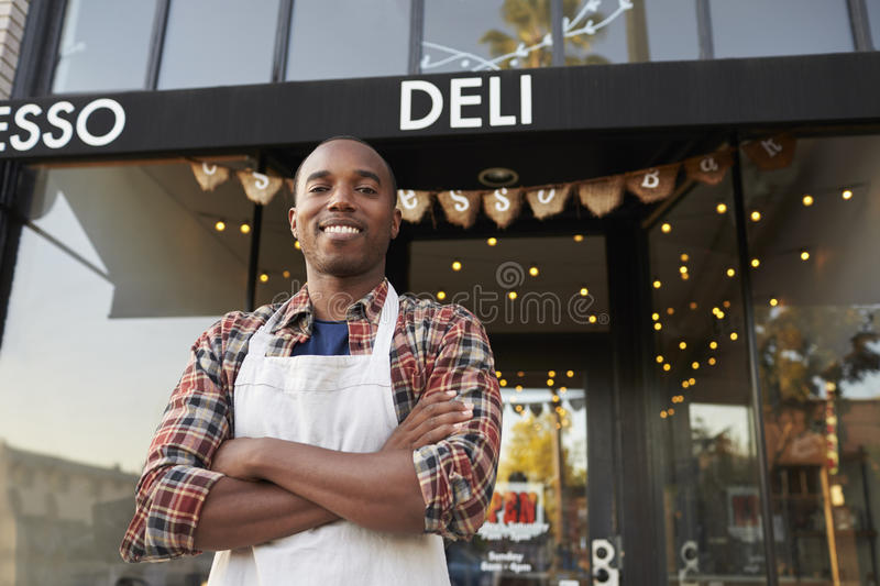 Black male business owner standing outside coffee shop stock photography