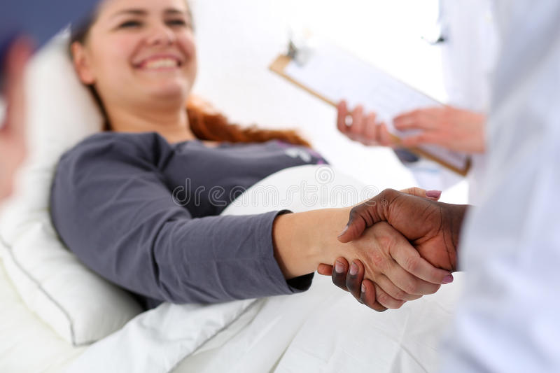 Black male doctor shake hands as hello with female patient royalty free stock photo