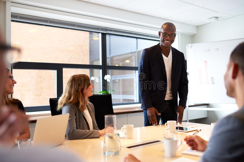 Black male executive standing and leading a work meeting royalty free stock image