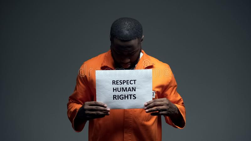 Black male prisoner holding respect human rights sign in cell, sexual harassment stock photo