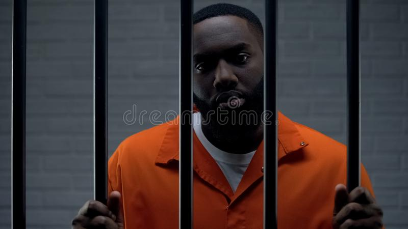 Black male prisoner waiting for sentence in prison cell, looking sadly to camera stock photography