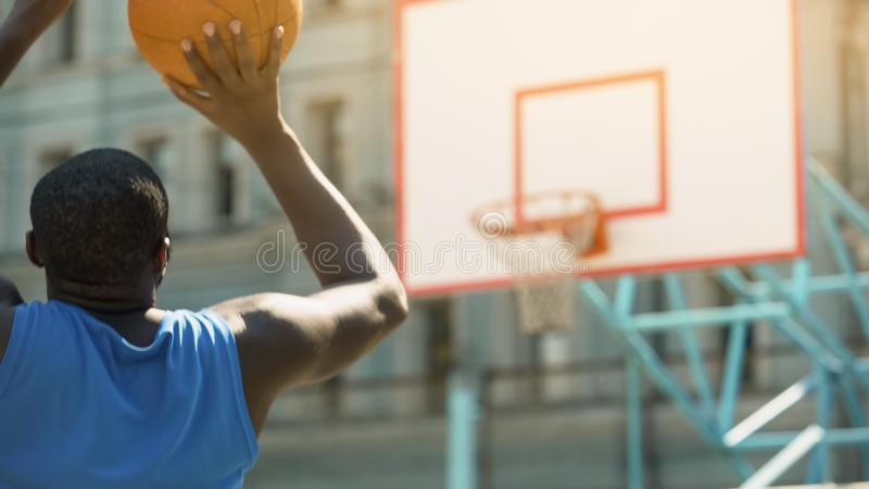 Black male in sportswear throwing ball into basket, active lifestyle and sport royalty free stock images
