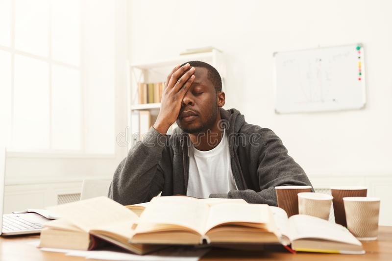 Black male student studying at table full of books royalty free stock image