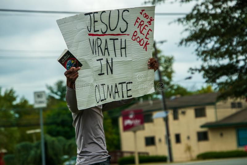 A black male was seen standing by the side of a busy road with a sign that says Jesus Wrath In Climate royalty free stock photography