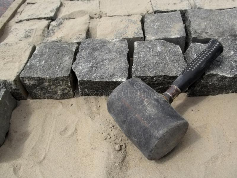 Black Mallet close-up on a background of square granite stones and sand royalty free stock image