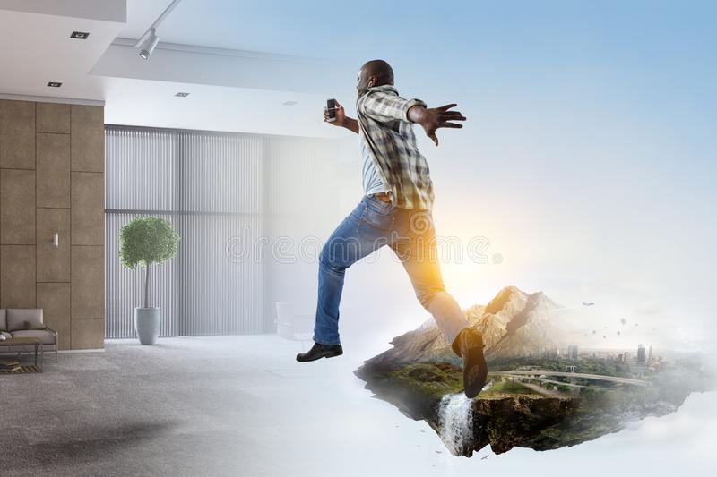 Black man in casual clothes in motion. Black man in casual clothes running, natural landscape mixed with a room environment royalty free stock photography