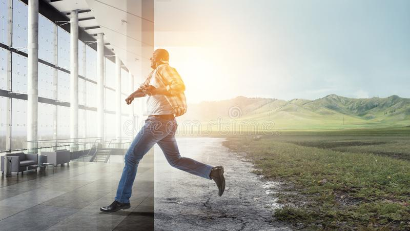 Black man in casual clothes in motion. Black man in casual clothes running pleased, environment mixture of natural landscape and a hall stock photography