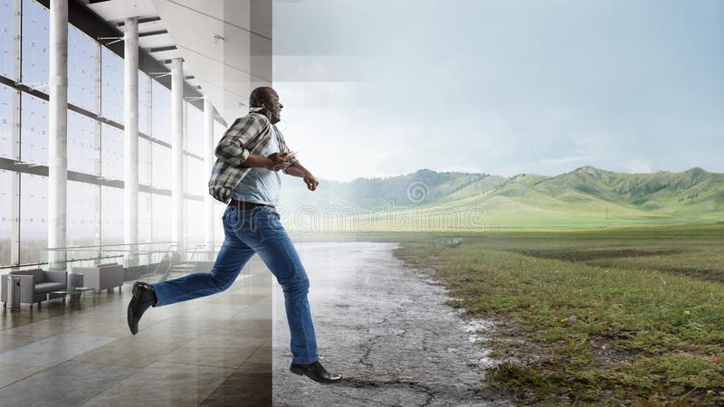 Black man in casual clothes in motion. Black man in casual clothes running pleased, environment mixture of natural landscape and a hall royalty free stock images