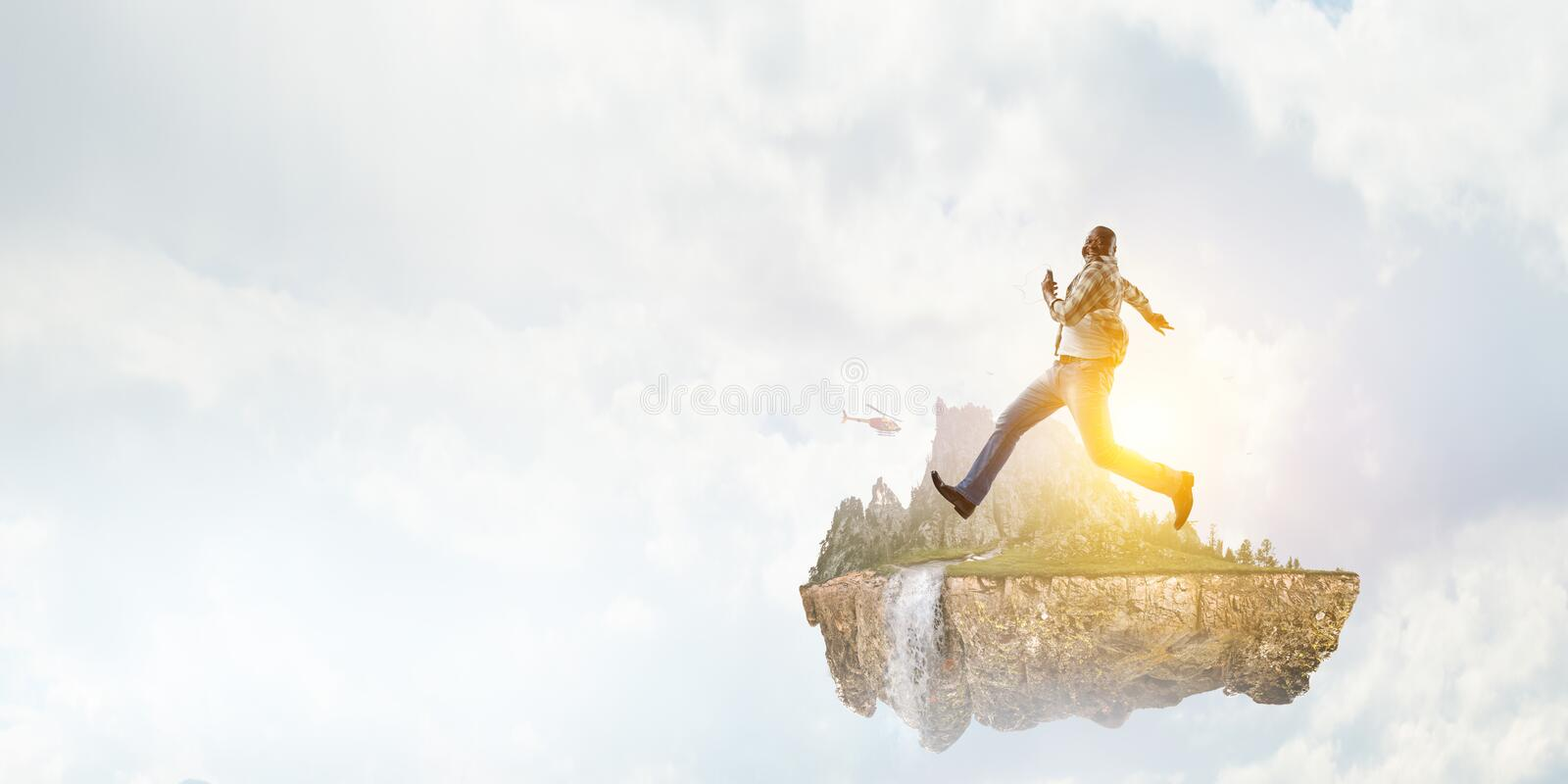 Black man in casual clothes in motion. Happy black man in casual clothes running on natural landscape against white cloudy sky background royalty free stock image