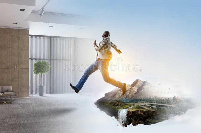 Black man in casual clothes in motion. Happy black man in casual clothes running, natural landscape mixed with a room environment royalty free stock image