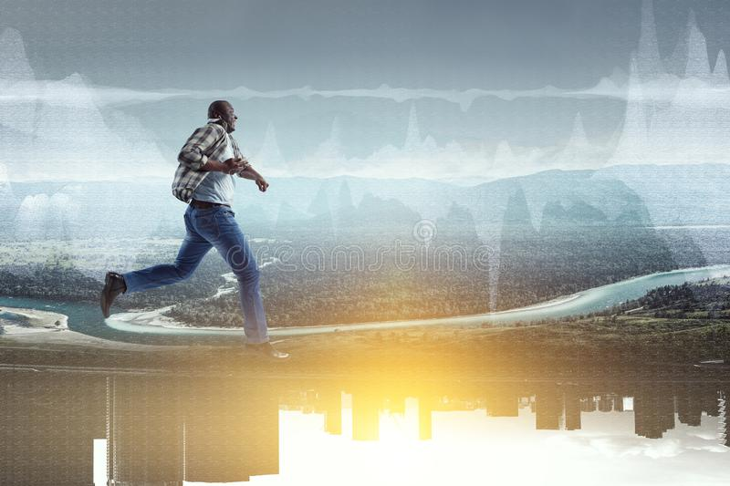 Black man in casual clothes in motion. Happy black man in casual clothes running on natural landscape with urban buildings stock image