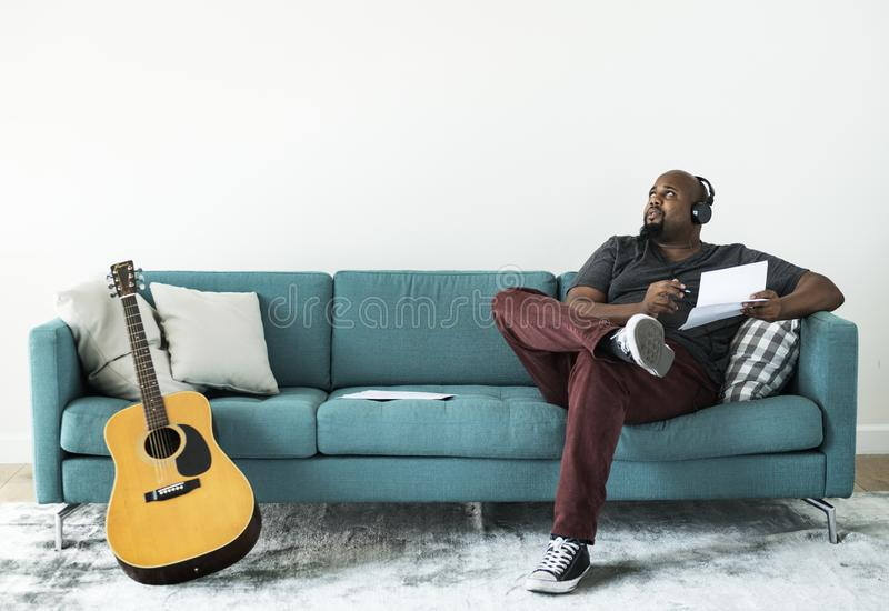 Black man composing new song on a couch royalty free stock photos