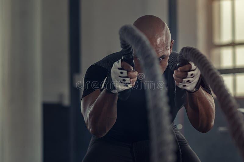 Black man doing intensive battle rope workout royalty free stock photo