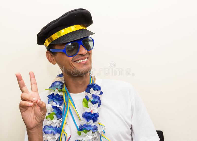Black man is dressed as a captain or pilot, wearing a cap. He ma. Black man is dressed as a captain or pilot. He is wearing sunglasses and Hawaiian necklace at a royalty free stock photos