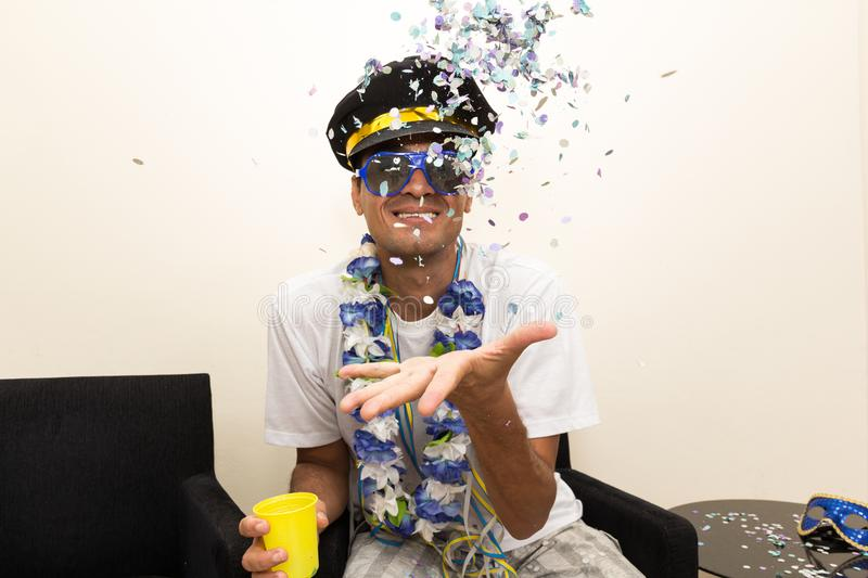 Black man is dressed as a captain or pilot, wearing a cap. Brazilian throws confetti to the top.. royalty free stock photo