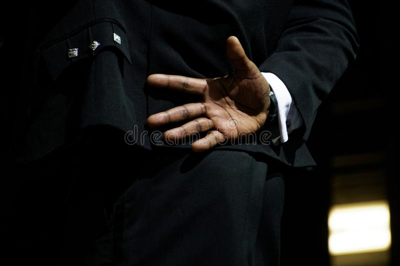 A black man in an elegant suit hid his hand behind his back, not wanting to say hello. Fear of communication, isolation and. Introversion. On a dark background stock images